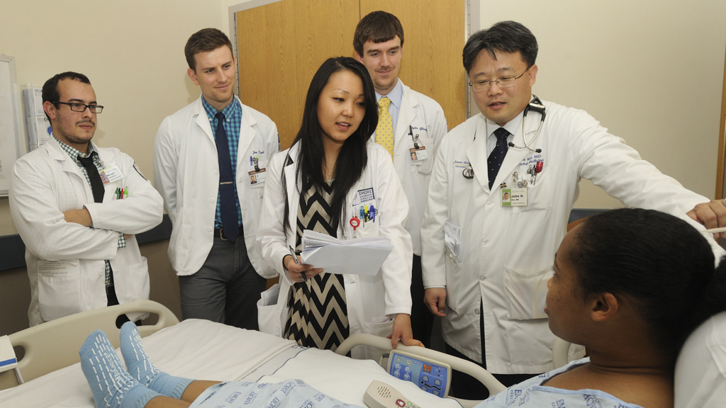 Students with faculty member rounding at bedside