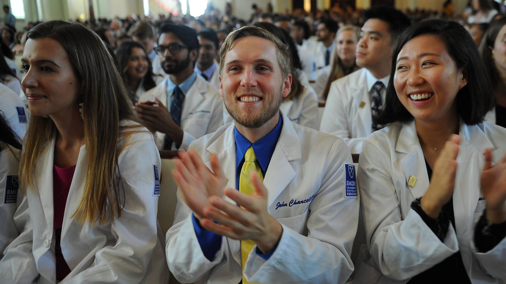 students in white coats sitting in a full audience