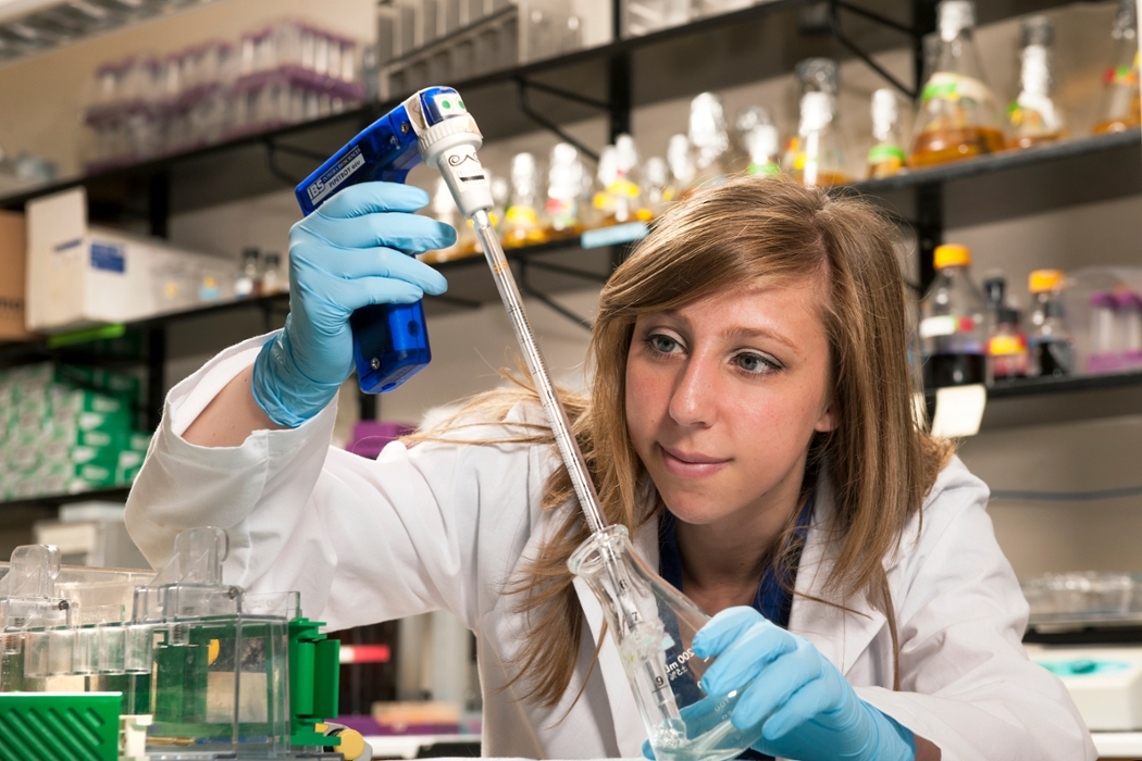 Female student using pipette and flask